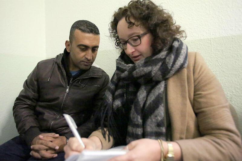Migrationsberaterin berät einen Geflüchteten
