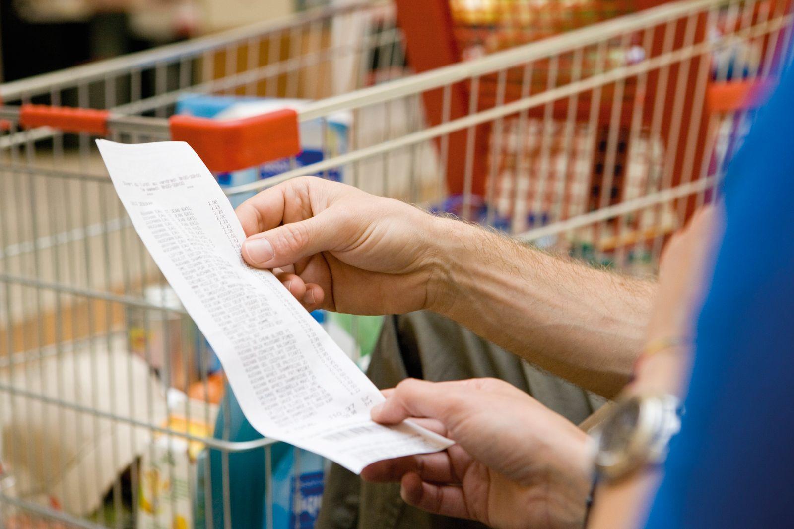 Eine Person hält einen Kassenzettel in der Hand