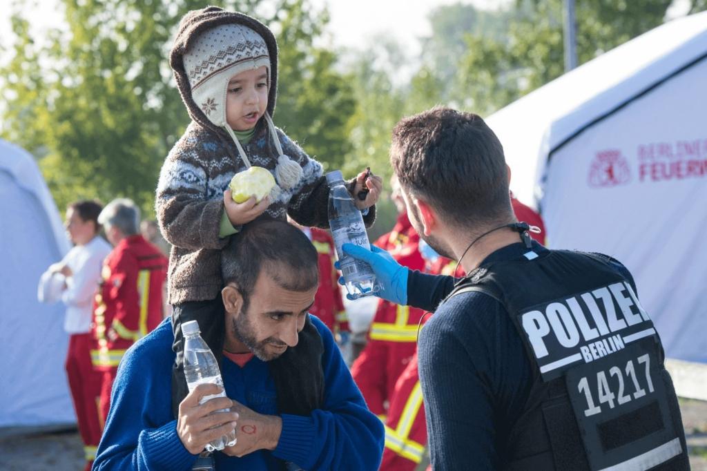 Polizist mit einem Geflüchtetem und seinem Kind
