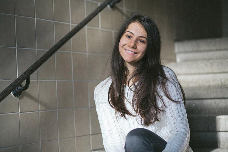 Eine junge Frau sitzt auf einer Treppe