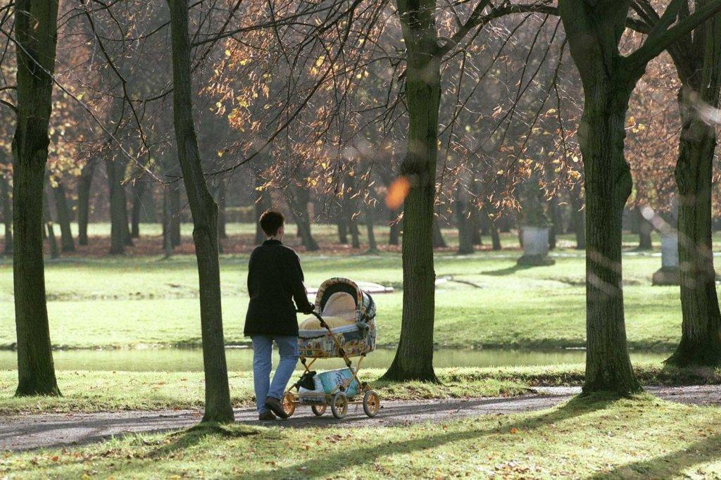 Herbstspaziergang im Schlosspark, Frau mit Kinderwagen
