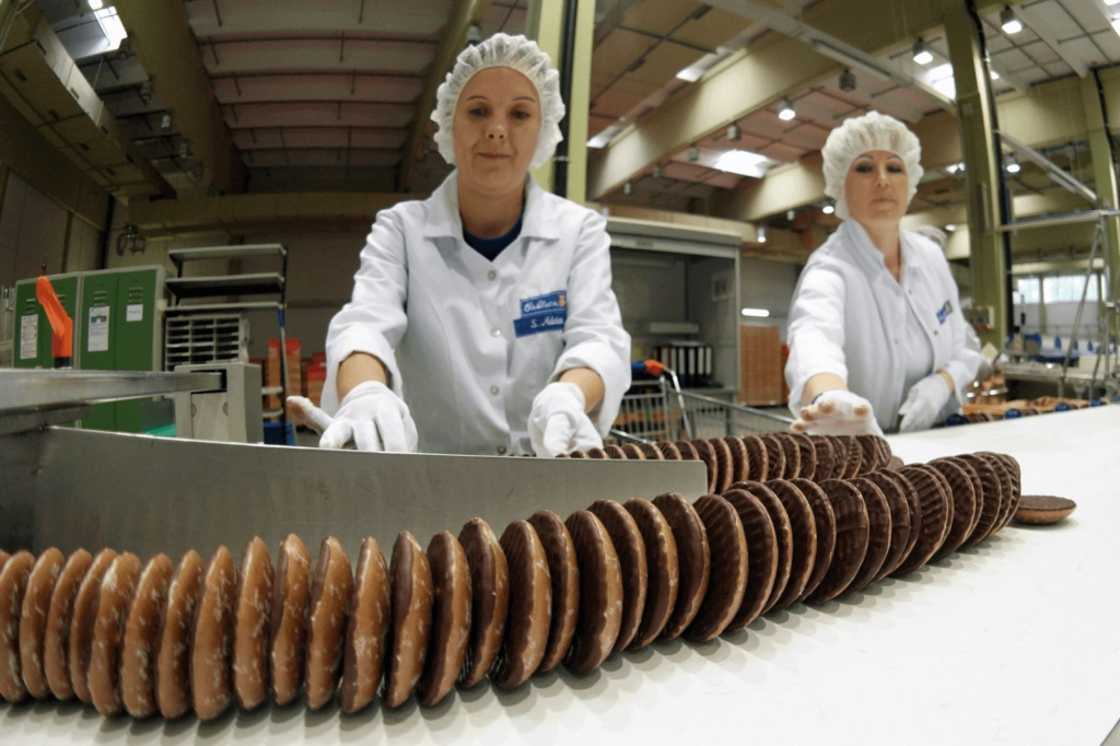 Women working at a conveyor belt making gingerbread cookies